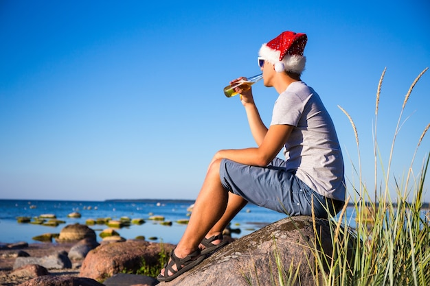 Kerstconcept - jonge knappe man in kerstmuts die bier drinkt op het strand