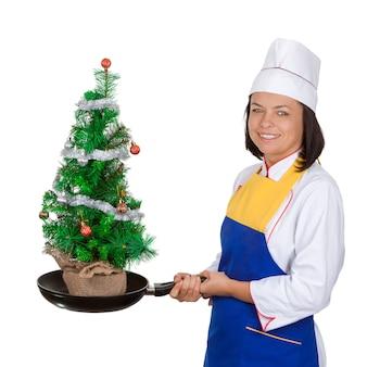Kerstconcept. mooie jonge vrouw chef-kok met versierde kerstboom in koekenpan op een witte achtergrond