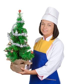 Kerstconcept. mooie jonge vrouw chef-kok met versierde kerstboom op een witte achtergrond