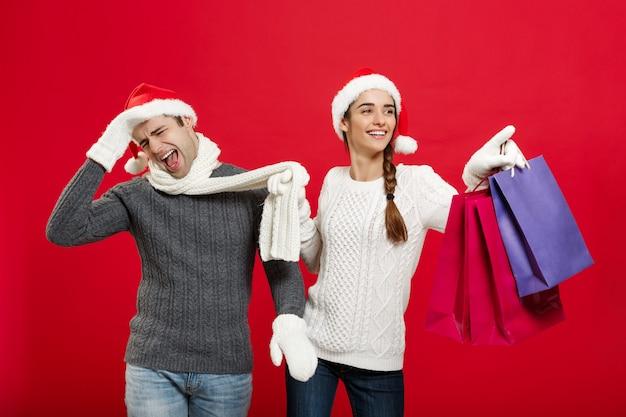 Kerstconcept - mooie vriendin dwingt haar vriendje te gaan winkelen over de rode kerstmuur.