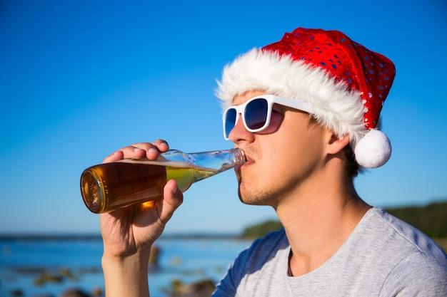 Kerstconcept - portret van een jonge man in een kerstmuts die bier drinkt op het strand