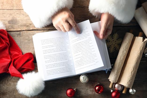 Kerstconcept. santa handen met boek en kerstversiering op houten tafel, close-up