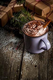 Kerstconcept, warme chocolademelk of cacao met slagroom en kruiden, kerstcadeaus, snoepgoed, kerstboomtak en dennenappels
