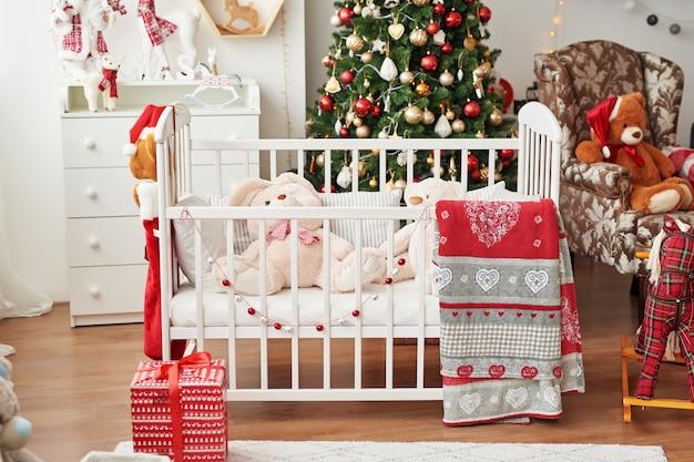 Kerstdagverblijf, kerstdecor in kinderkamer, kinderspeelkamer ingericht voor nieuwjaar, witte kinderkamer. kerstmisspeelgoed en geschenken in de kinderkamer, wit bed met zacht speelgoed