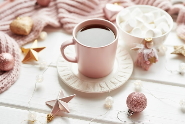 Kerstdecor, ballen, wollen plaid op het raam, huiscomfortconcept, seizoensgebonden wintervieringen. . kerstmis roze kop met marshmallow.