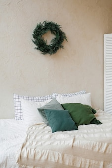 Kerstdecor in de slaapkamer en een krans aan de muur in het interieur in scandinavische stijl