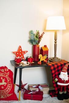 Kerstdecor in huis: een tas met cadeautjes, een vaas met sparren takken en speelgoed in rode kleuren