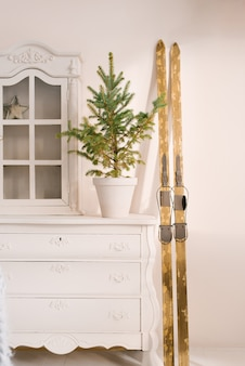Kerstdecor in huis. vintage houten ski's, een dennenboom in een pot op het dressoir