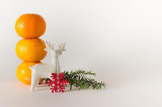 Kerstdecor mandarijnen, groenblijvende tak en wit porseleinen rendieren op wit oppervlak met kopie lege ruimte.