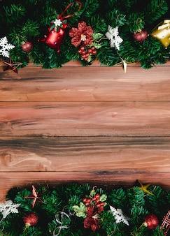 Kerstdecoratie achtergrond met kopieerruimte in middelste horizontale lay-out, nep dennentakken en kerstversieringen decoratieve rekwisieten aan boven- en onderrand, bovenaanzicht.