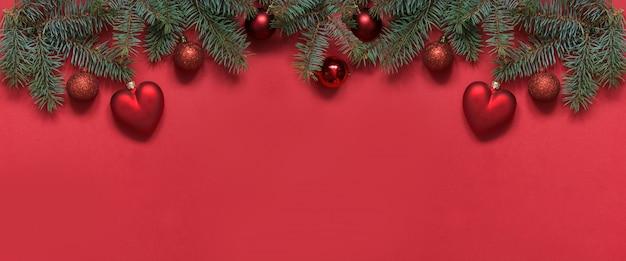 Kerstdecoratie achtergrond van rode ballen en hart, groenblijvende takken op rood. bovenaanzicht, platliggend. kerstmis.