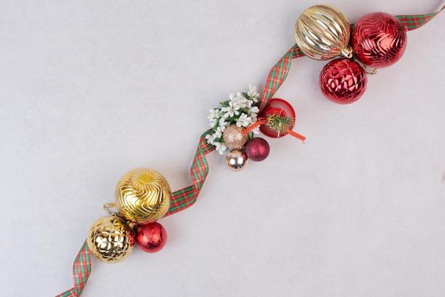 Kerstdecoratie ballen met band op witte tafel.