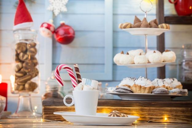 Kerstdecoratie bar cacao met koekjes en snoep op blauwe houten achtergrond in vintage stijl