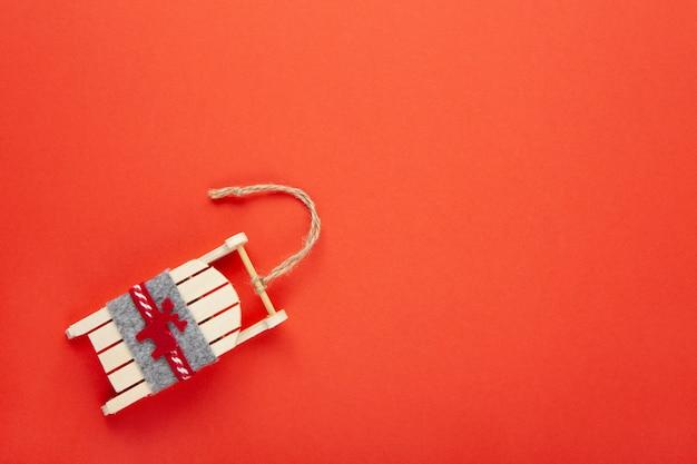 Kerstdecoratie, boom speelgoed, houten slee met herten op rood