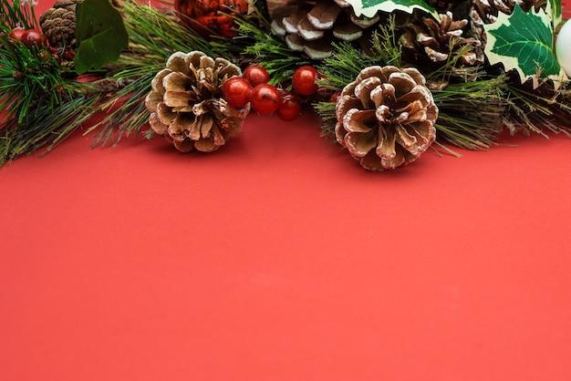 Kerstdecoratie dennen tak in sneeuw bessen en dennenappel op rood