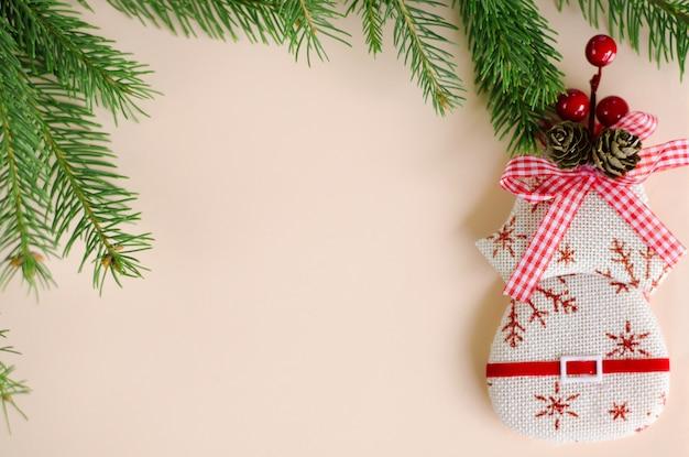 Kerstdecoratie-elementen en tak van spar op pastel. copyspace