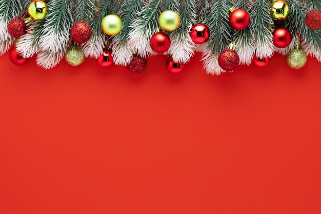 Kerstdecoratie fir tree takken met sneeuw, gouden rode ballen op rode achtergrond samenstelling