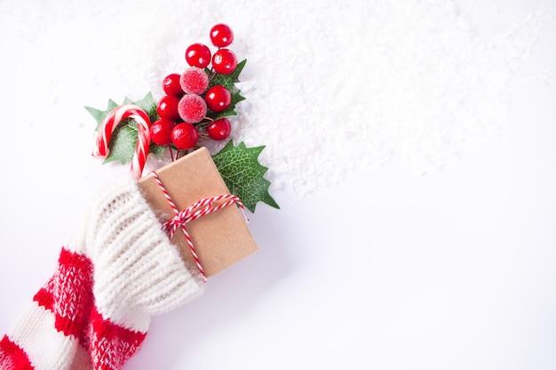 Kerstdecoratie gebreide sok met zuurstok, geschenkdoos en bes. bovenaanzicht. kopieer ruimte.