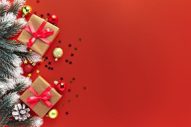 Kerstdecoratie geschenken huidige doos, fir tree takken, ballen op rode achtergrond. nieuwjaar