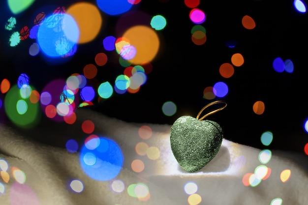 Kerstdecoratie hart in de sneeuw. intreepupil lichten op de achtergrond. decoratie voor de kerstboom. kerst achtergrond