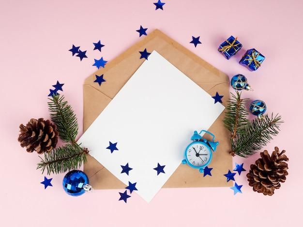 Kerstdecoratie in envelop. vuren tak op roze tafel
