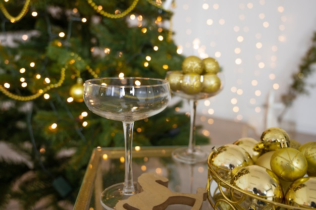 Kerstdecoratie in gouden kleur met glazen champagne.