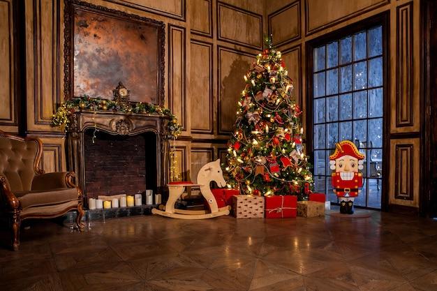Kerstdecoratie in grunge kamer interieur met open haard, paard schommelende kinderstoel, klassieke boom met cadeautjes