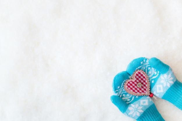 Kerstdecoratie in kinderen handen op sneeuw