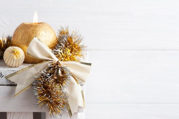 Kerstdecoratie in scandinavisch interieur met gouden strik, ballen en aangestoken kaars. kopieer ruimte voor begroeting