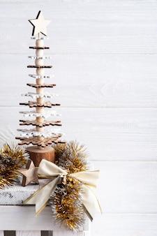 Kerstdecoratie in scandinavisch interieur met gouden strik, ster en houten boom. kopieer ruimte voor begroeting
