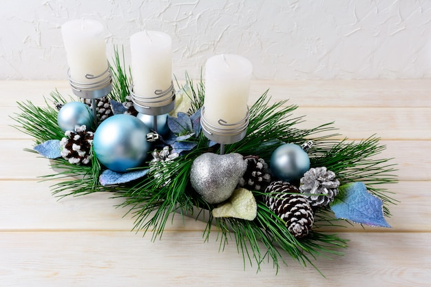 Kerstdecoratie met blauwe ornamenten versierde kandelaar