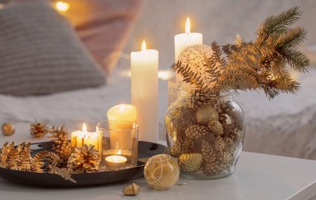 Kerstdecoratie met brandende kaarsen op witte tafel tegen de achtergrond van de bank met plaids en kussens. gezellig huis- en vakantieconcept