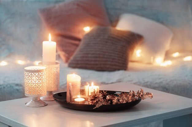 Kerstdecoratie met brandende kaarsen op witte tafel tegen de achtergrond van een bank met plaids en kussens. gezellig huis- en vakantieconcept
