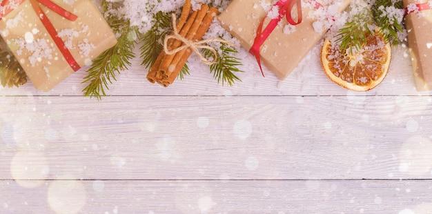 Kerstdecoratie met cadeautjes, sneeuw, sinaasappel en kaneelstokjes