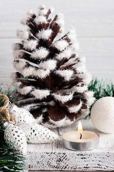 Kerstdecoratie met dennenappel en aangestoken kaars op witte rustieke achtergrond. kopieer ruimte voor begroeting