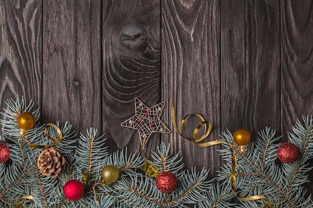 Kerstdecoratie met dennentakken en rode en gouden kerstballen op donkere houten achtergrond met kopieerruimte