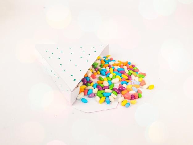 Kerstdecoratie met geopende driehoek git doos met kleurrijke snoep