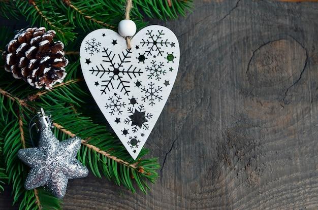 Kerstdecoratie met hangend hart met sneeuwvlokken en dennenappel