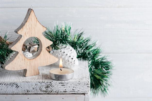 Kerstdecoratie met houten sterren en aangestoken kaars op wit rustiek oppervlak. kopieer ruimte voor begroeting