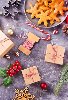 Kerstdecoratie met kegels, koekjes, geschenkdozen, rode kaarsen, snoepjes. bovenaanzicht.