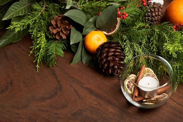 Kerstdecoratie met kerstboomtak, mandarijn en dennenboomkegels