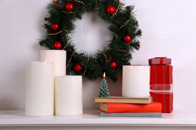 Kerstdecoratie met krans en kaarsen op plank op witte muur oppervlak