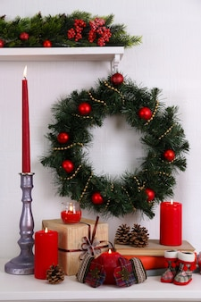 Kerstdecoratie met krans, kaarsen en cadeaudozen op plank op witte muur