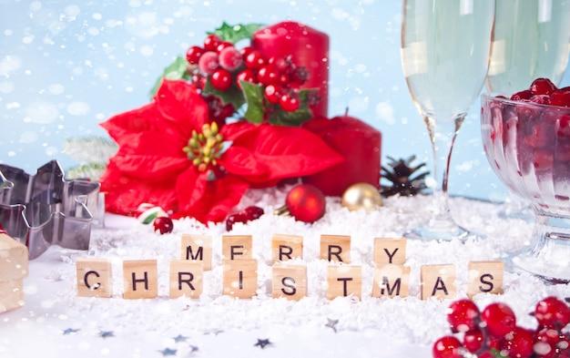 Kerstdecoratie met poinsettia bloem, bessen, rode kaarsen met tekst merry christmas met houten woorden.