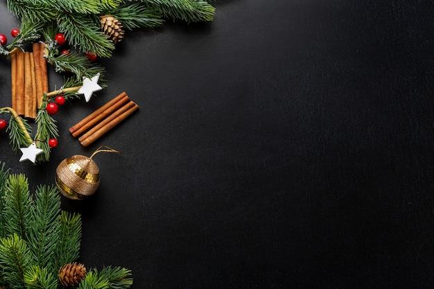 Kerstdecoratie met sparren en kerstballen op donkere achtergrond. plat leggen. kerst concept