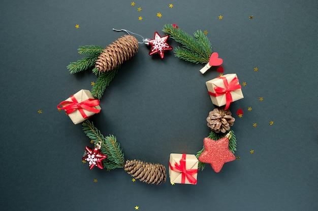 Kerstdecoratie met takken, sterren, geschenkdozen en dennenappel, afgeronde frame op zwarte achtergrond