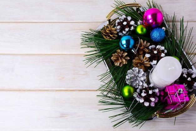 Kerstdecoratie met vakantieornamenten, kaars en dennenappels middelpunt