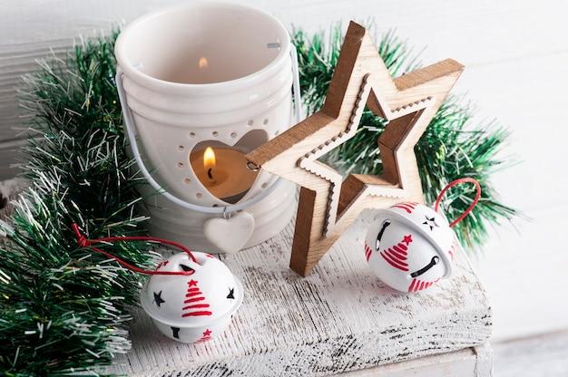 Kerstdecoratie met witte jingle bells en kaars op wit rustiek oppervlak