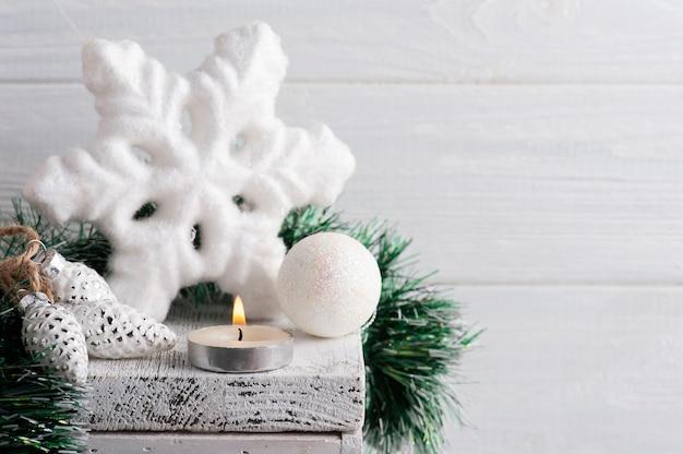 Kerstdecoratie met witte ster en aangestoken kaars op wit rustiek oppervlak. kopieer ruimte voor begroeting