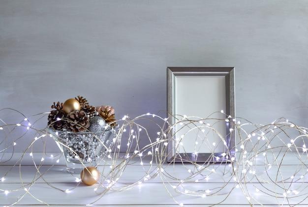 Kerstdecoratie mock-up in een frame met kegels kerstverlichting op een witte tafel kopieerruimte